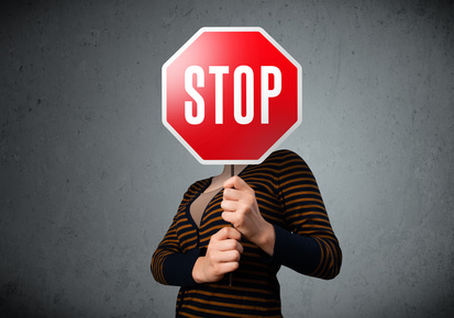 Young lady standing and holding a stop sign in front of her head
