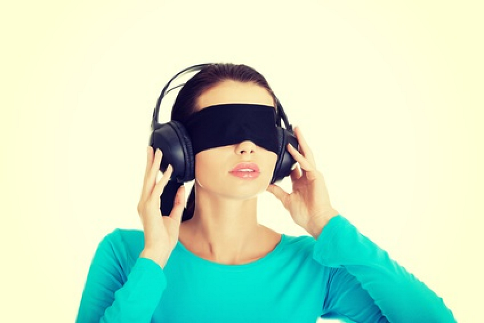 Woman who is blindfolded and listening to headphones