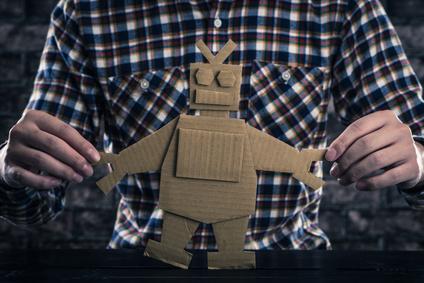 Man holding cardboard cutout of a robot