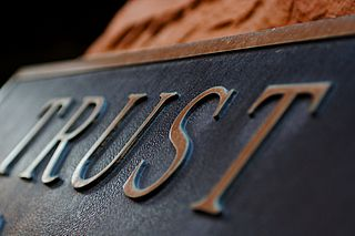 Metal plaque with the word TRUST in raised letters, originally posted to Flickr by Terry Johnston under the terms of the cc-by-2.0.