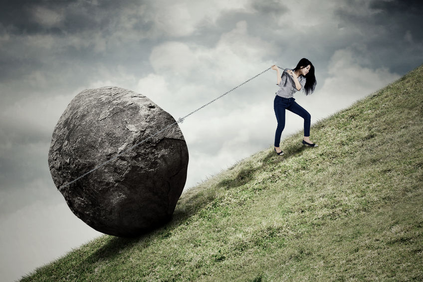 Image of young businesswoman climbing on the hill while pulling big stone with a chain