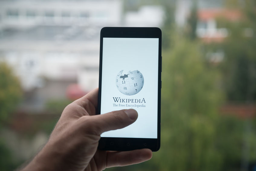Hand holidng a mobile phone showing the Wikipedia home screen