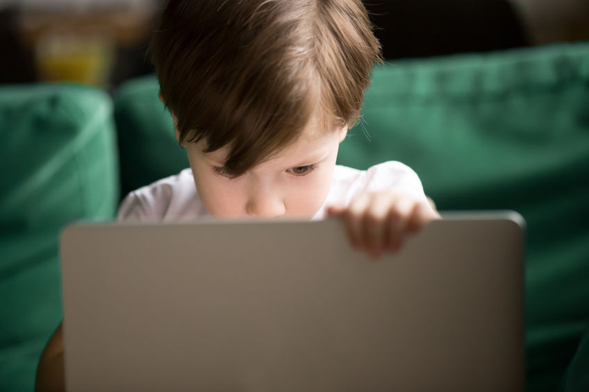 Curious interested kid boy secretly looking watching forbidden censored adult only internet online video content on laptop alone, parental protection, computer control and security for child concept