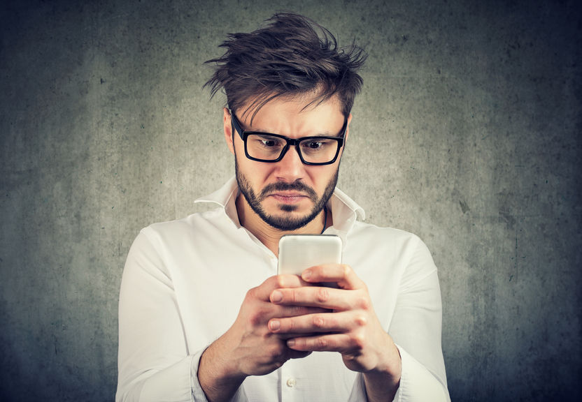 stunned man, surprised offended, shocked by what he sees on his smartphone