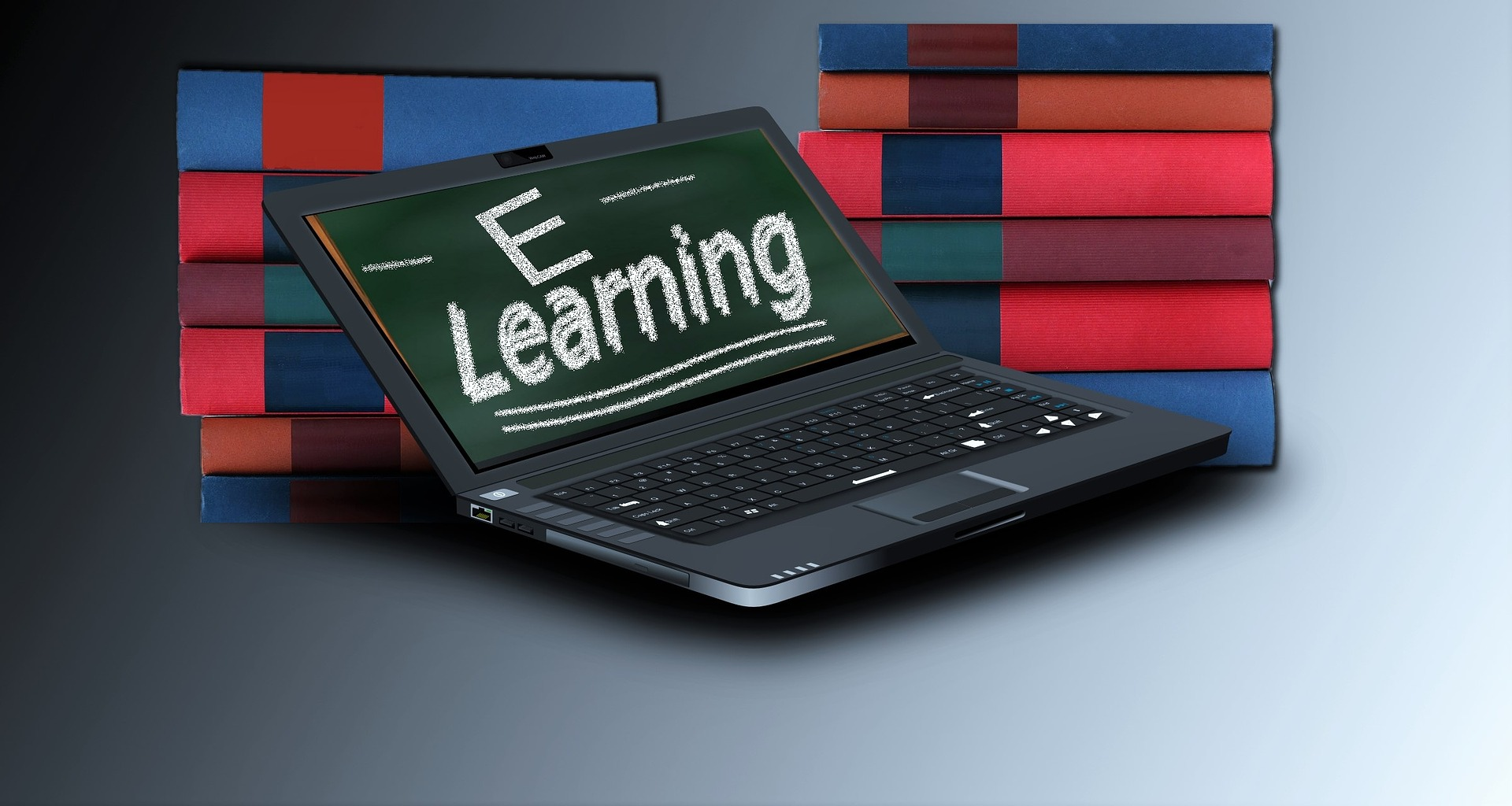 "Laptop with the words ""e-learning"" on screen set against a backdrop of books"