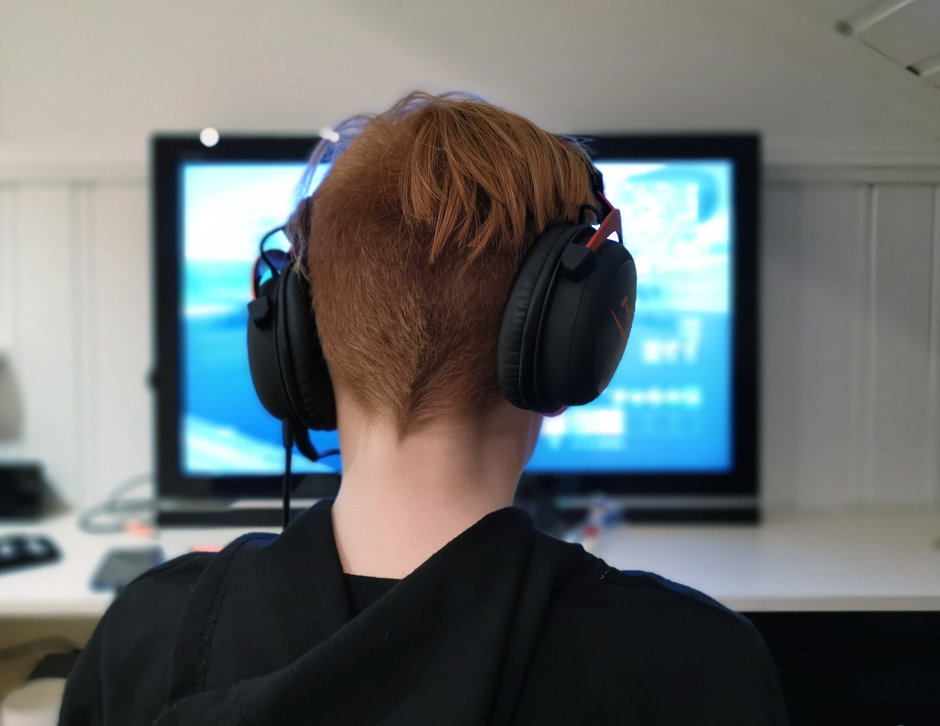 Teen with headset playing a computer game