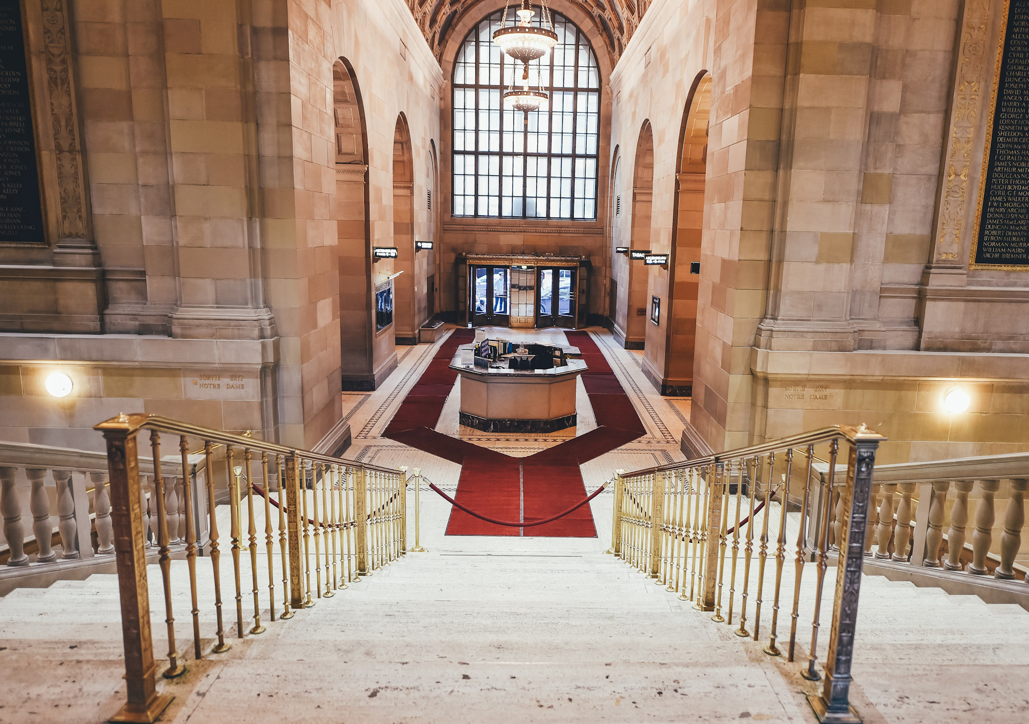 View down the stairs of a fancy building, ending in a velvet rope