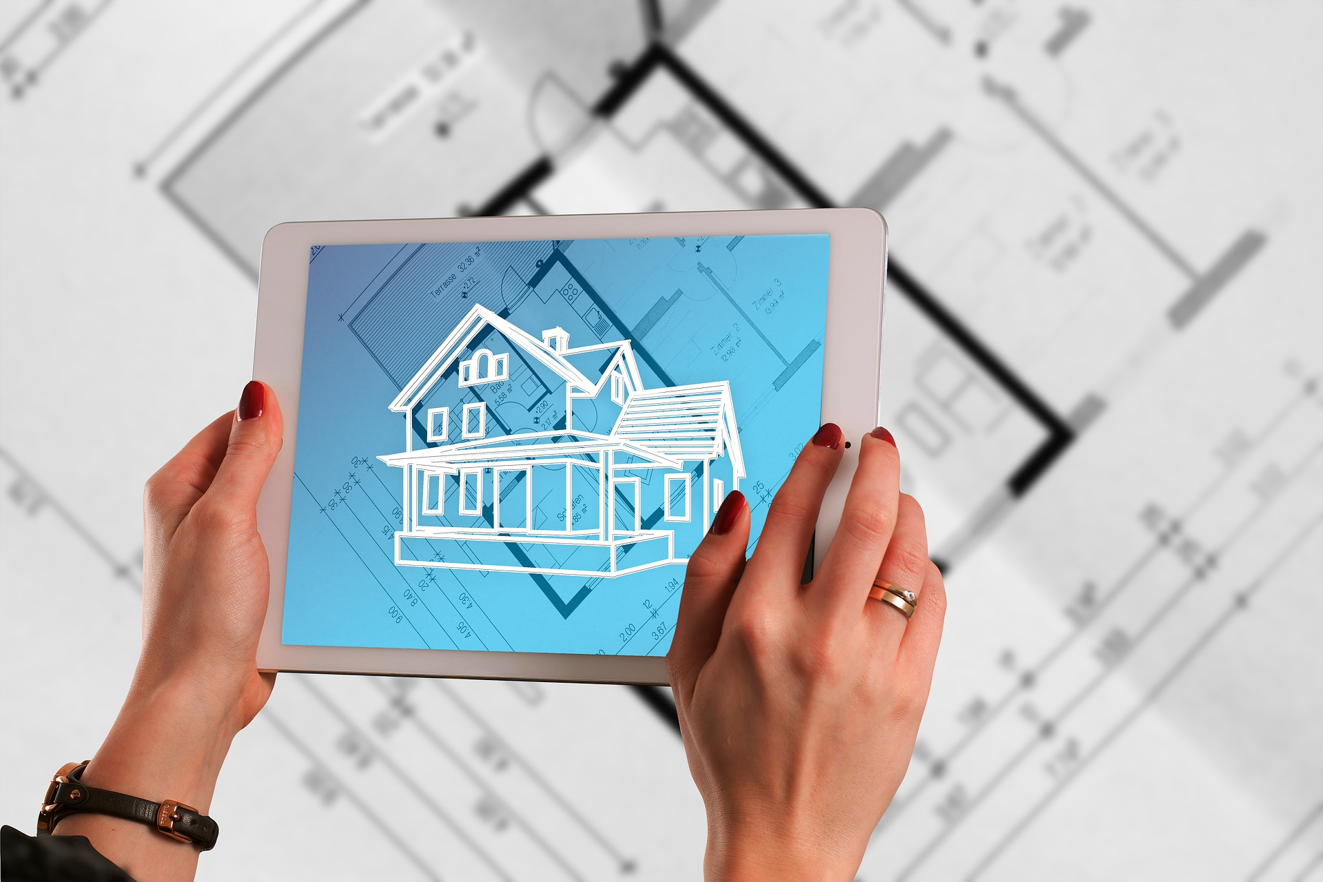 Augmented reality house appearing on tablet held over blueprints