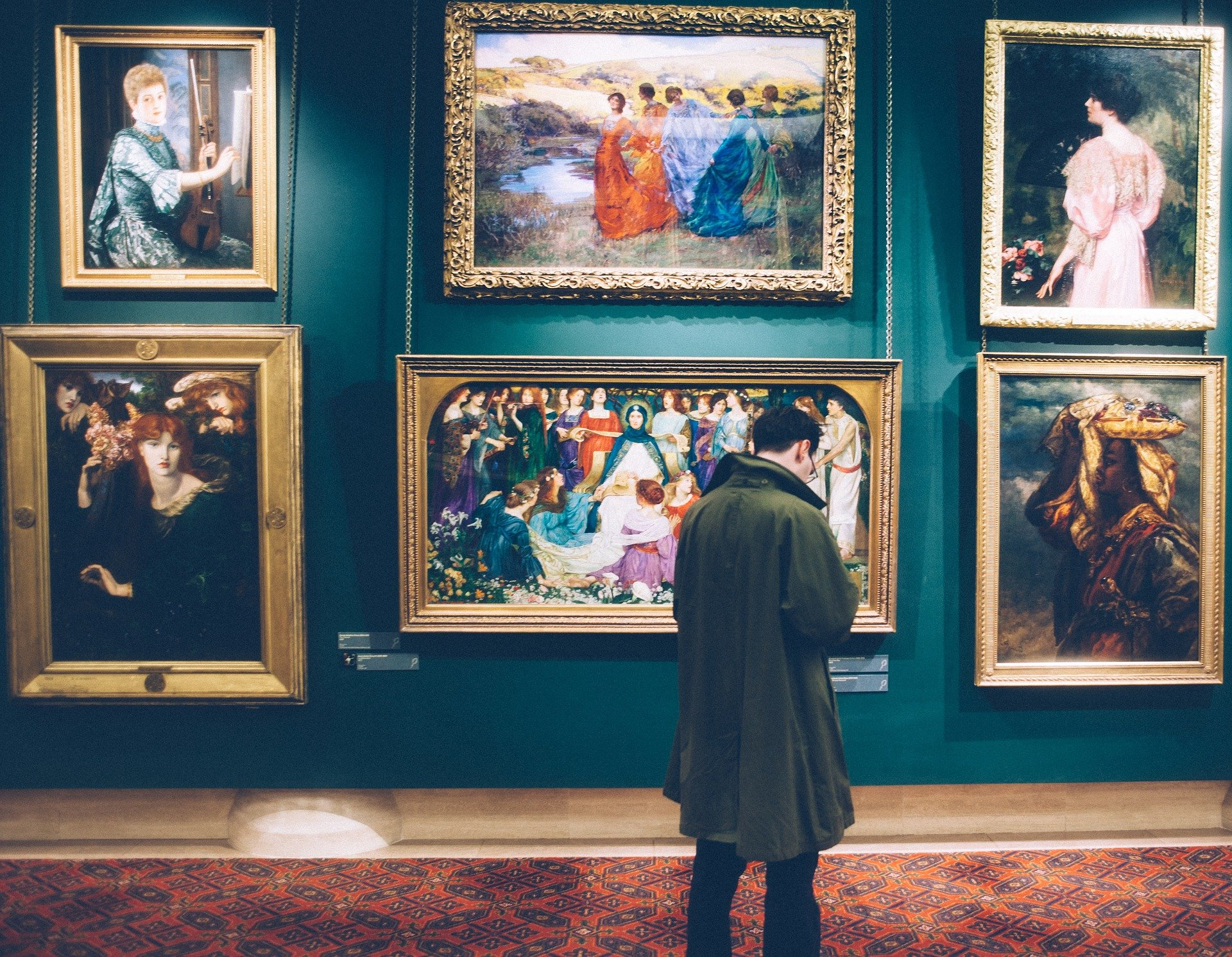Man looking at paintings on wall of a museum