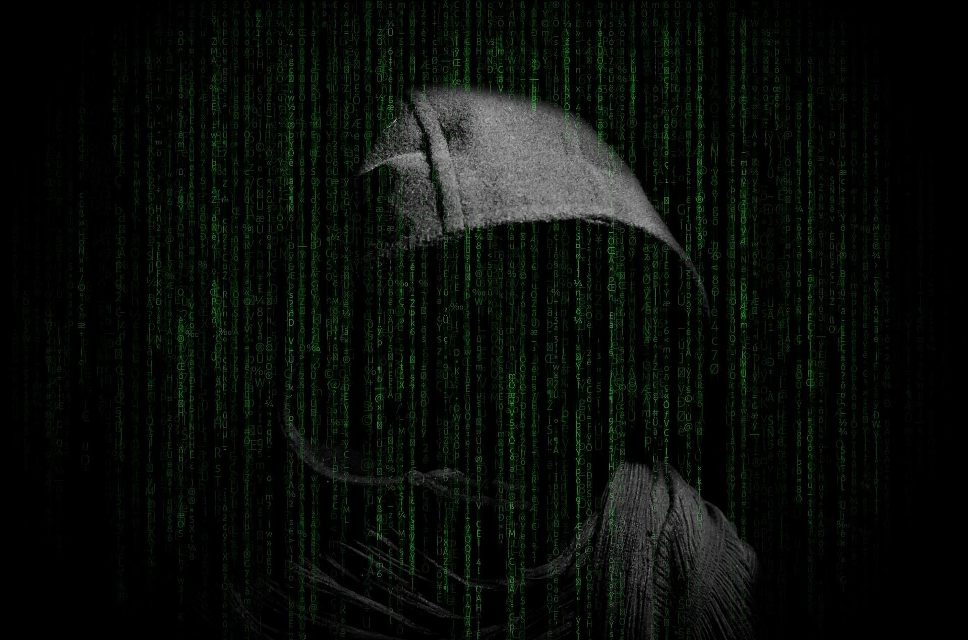 Man in dark hood with digital background
