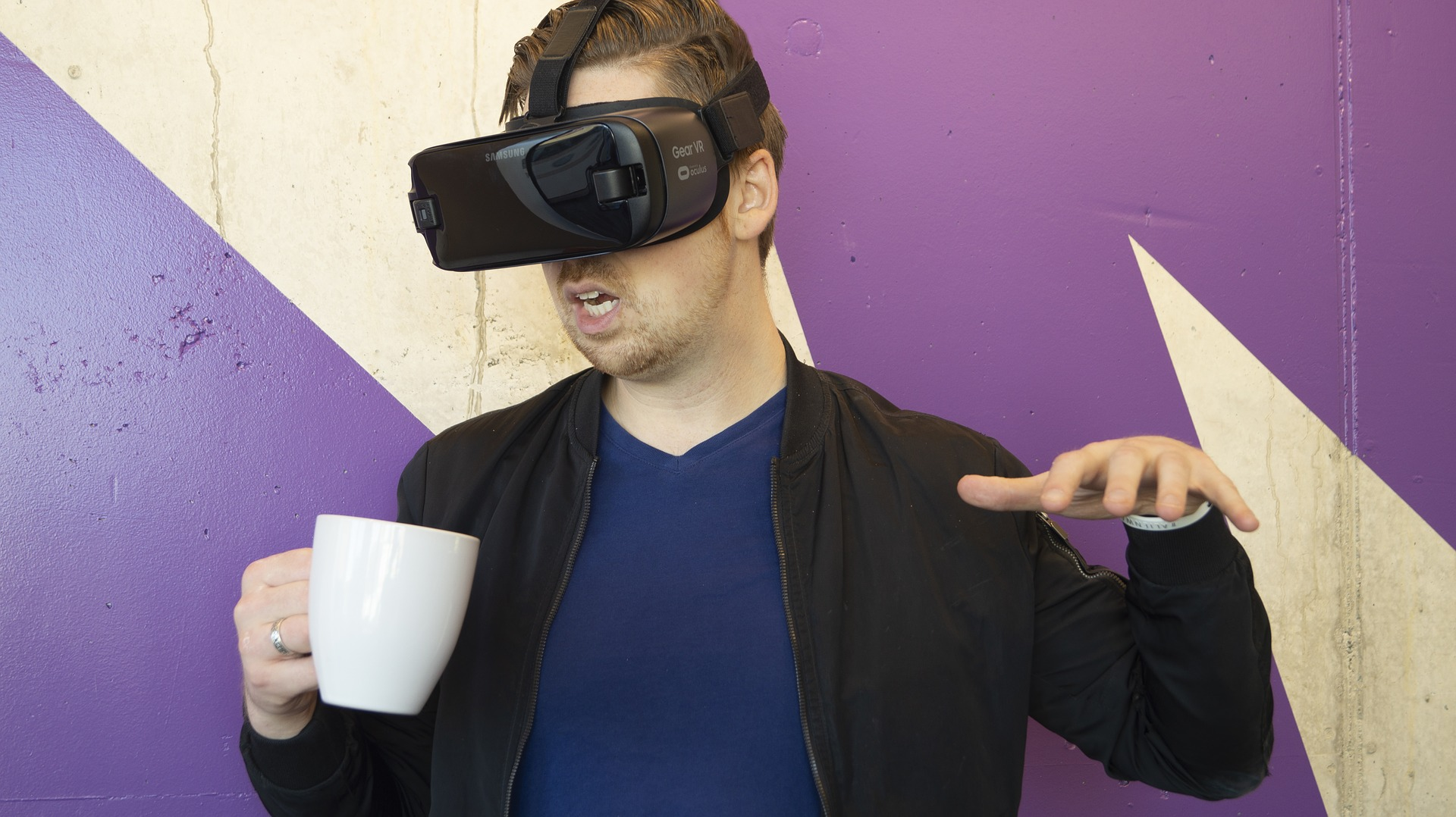 Man wearing a VR headset and holding a mug